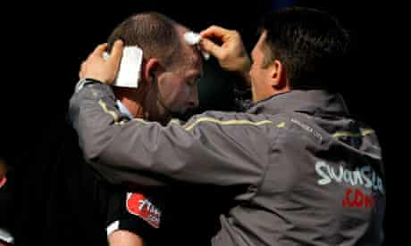 Referee Mike Dean receives medical attention during the clash between Cardiff City and Swansea City