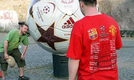 Manchester United fans pose in front of a giant football at Ponte Milvio