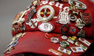 An Arsenal fan shows off his badges