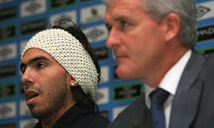 Carlos Tevez sits beside Mark Hughes at his Manchester City unveiling