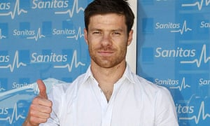 Xabi Alonso poses for photos after passing a medical at Real Madrid