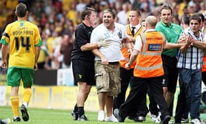 Two Norwich fans are escorted off the pitch