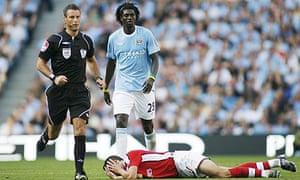 Robin van Persie holds his face following a challenge by Emmanuel Adebayor