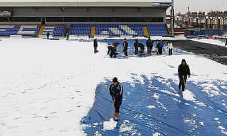 Volunteers help clear snow from the pitch at Macclesfield Town