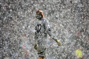 Football white-outs: Bolton goalkeeper Jussi Jaaskelainen looks to the heavens as snow falls