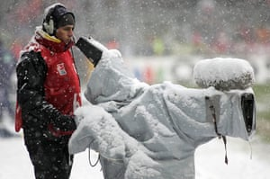 Football white-outs: A cameraman handles his snow covered camera
