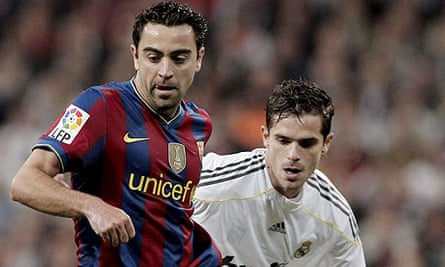 Barcelona's Xavi holds off Real Madrid's Fernando Gago