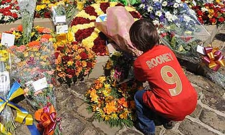 A young fan lays a floral tribute at the Valley Parade Memorial