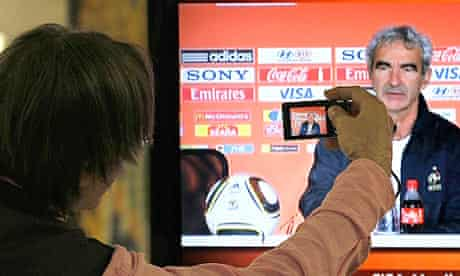 A journalist takes a picture on a TV screen of France coach Raymond Domenech