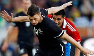 Paraguay's Oscar Cardozo fights for the ball with New Zealand's Tommy Smith