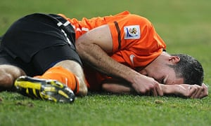 Robin van Persie clutches his arm in pain during Holland's win over Brazil