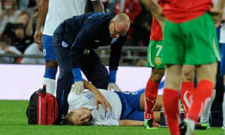 Michael Dawson lies on the ground after injuring his knee against Bulgaria