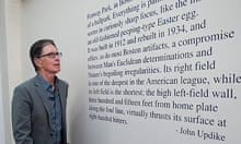 John W Henry standing next to a quote from John Updike painted on the wall at Fenway Park