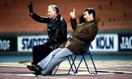 Brian Clough and Peter Taylor sit watching from the running track during Forest's second-leg win