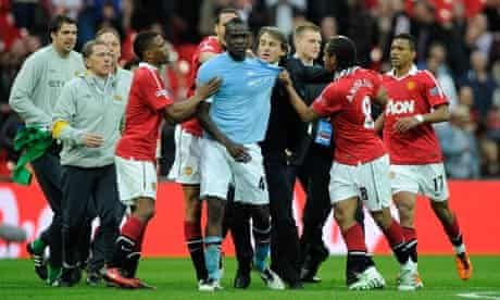 Roberto Mancini drags Mario Balotelli out of trouble the last time both Manchester clubs met