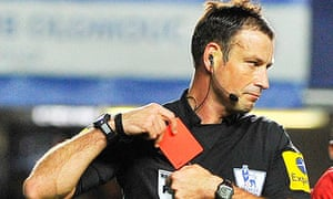 Referee Mark Clattenburg holds a red card