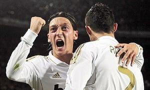 Real Madrid's Mesut Ozil, left, congratulates Cristiano Ronaldo on his winning goal at Barcelona