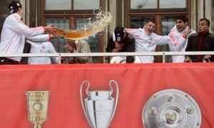Bayern Munich defender Daniel van Buyten throws beer on his team-mates on the balcony