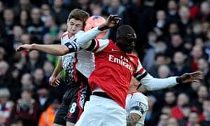 Steven Gerrard of Liverpool goes up with Yaya Sanogo of Arsenal
