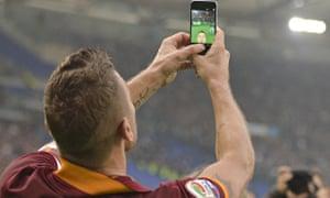 Roma's Francesco Totti celebrates taking a selfie after scoring against Lazio