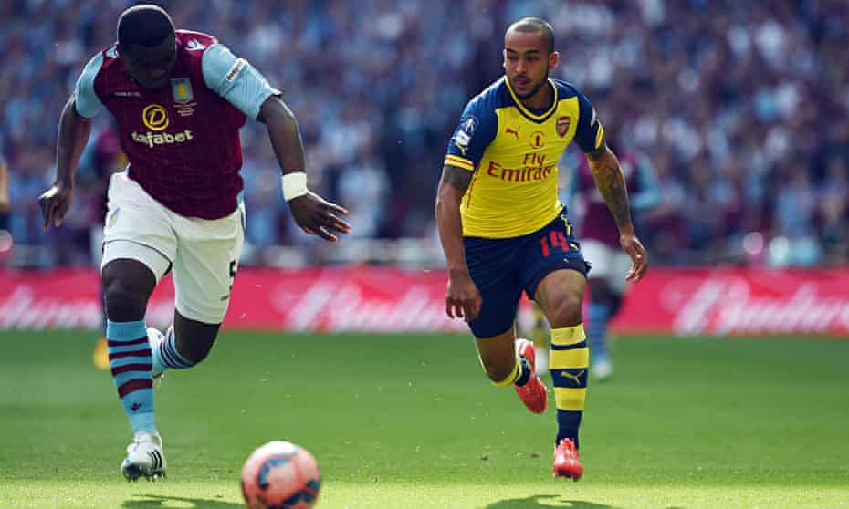 Theo Walcott forces the Aston Villa centre-back Jores Okore into retreat as the Arsenal forward used