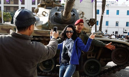 Tunisian woman poses in front of tank