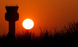 The sun sets behind the air traffic control tower at East Midlands Airport