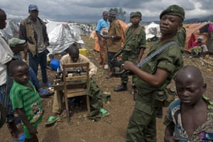Gallery Conflict in Congo: A Government soldier talks to displaced people in a refugee camp in Kibati