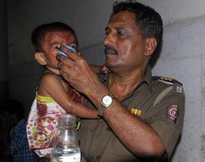Gallery Mumbai terror attacks: A policeman gives water to an injured child at a hospital in Mumbai