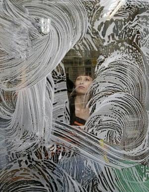 Gallery November 7 2008: Warsaw, Poland: A woman cleans a window at an antiquarian bookshop