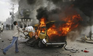 A Palestinian tries to extinguish a fire in a car