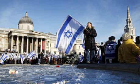 A Jewish demonstrator waves an Israeli flag beside a frozen fountain in Trafalgar Square