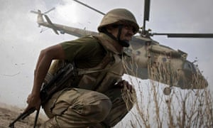 Pakistani soldier crouches a helicopter takes off in South Waziristan