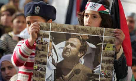Palestinian children hold a poster of Marwan Barghouti