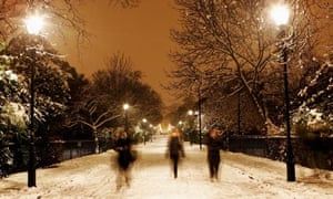 People walk in Victoria Park as the snow continues to fall in London