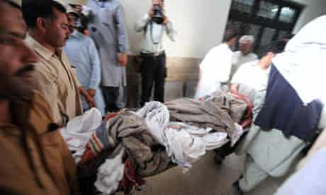 Relatives carry the body of a suicide blast victim at a hospital in Chakwal, Pakistan