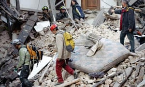 Rescuers search for trapped people after an earthquake in Aquila, Italy