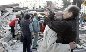 People stand amidst debris in the city of Aquila after a strong earthquake rocked central Italy