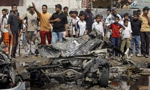 A crowd gathers at the site of a car bomb attack in the Sadr City neighbourhood of Baghdad, Iraq