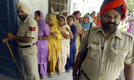 Indian elections: Policemen stand guard as voters wait to cast their ballot
