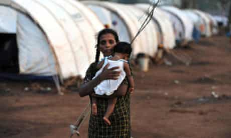 A displaced Tamil woman holds her baby at Manic Farm in the northern Sri Lankan district of Vavuniya