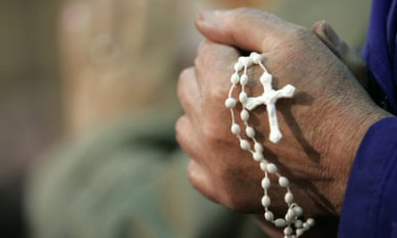 A rosary is held during prayer