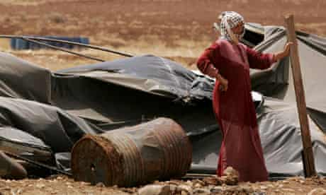 A Palestinian bedouin woman next to her destroyed tent in the village of Atouf in the Jordan Valley