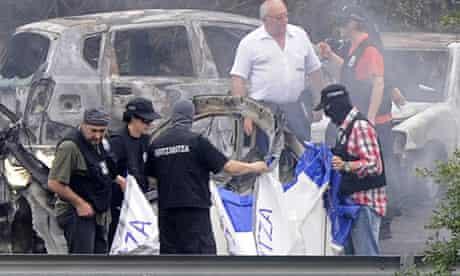 Police officers investigate the scene of a car bomb in Bilbao