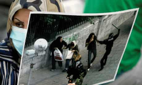 Iran protests: woman holds a picture of police brutality