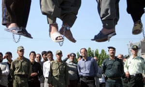 Iranian police officers and others view the scene as five convicted criminals are hanged in public