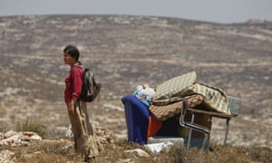 A Jewish settler stands next to ruins of a structure destroyed by Israelis