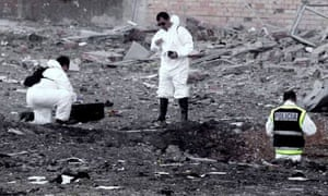 Forensic experts collect evidence next to a crater following the explosion of a car bomb in Burgos