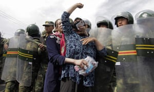 Protest by Uighurs against a line of security forces