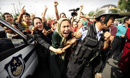 Ethnic Uighur women grab a riot policemen as they protest in Urumqi